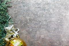 Weihnachtshintergrund mit goldenem Ball und Schnee auf hölzernem Brett Lizenzfreie Stockfotos