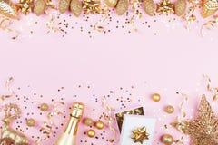 Weihnachtshintergrund mit goldenem Geschenk oder Präsentkarton, Champagner und Feiertagsdekorationen auf rosa Pastelltischplattea stockfotos