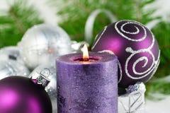 Weihnachtshintergrund mit Kerze und Dekorationen Purpurrote und silberne Weihnachtsbälle über Tannenbaumasten im Schnee stockfotografie