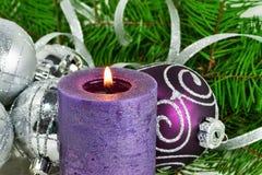 Weihnachtshintergrund mit Kerze und Dekorationen Purpurrote und silberne Weihnachtsbälle über Tannenbaumasten im Schnee Lizenzfreies Stockfoto
