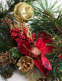 Weihnachtshintergrund mit Kieferniederlassung, Kiefernkegel, rote Blume im Schnee Lizenzfreie Stockbilder