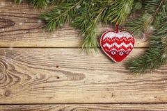 Weihnachtshintergrund mit Kiefernniederlassungen und gestricktem Herzen auf altem Lizenzfreies Stockbild