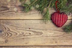 Weihnachtshintergrund mit Kiefernniederlassungen und gestricktem Herzen auf altem Stockbild