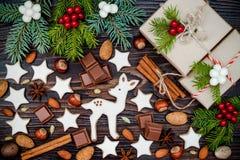 Weihnachtshintergrund mit Lebkuchenplätzchen, -geschenken, -Tannenzweigen und -gewürzen auf dem alten hölzernen Brett Stockfoto