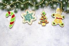 Weihnachtshintergrund mit lustigen Ingwerplätzchen und -Tannenzweigen Lizenzfreies Stockbild