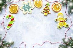 Weihnachtshintergrund mit lustigen Ingwerplätzchen und -Tannenzweigen Lizenzfreie Stockfotos