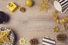 Weihnachtshintergrund mit modernen schwarzen und goldenen Dekorationen auf Holztisch Ansicht von oben Stockbild