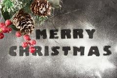 Weihnachtshintergrund mit Niederlassung des Weihnachtsbaums und der frohen Weihnachten der Wörter gemacht vom Puderzucker Kreativ Stockfoto