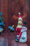 Weihnachtshintergrund mit Ren und einem Schneemann auf einem braunen Holz Stockbild