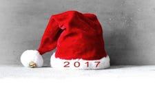 Weihnachtshintergrund mit rotem Hut Sankt auf weißem Schnee 2017 Lizenzfreie Stockfotos