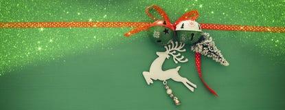 Weihnachtshintergrund mit rotem silk traditionellem Band, weißen Rotwild, immergrünem Baum und Klingelglocken Lizenzfreies Stockbild