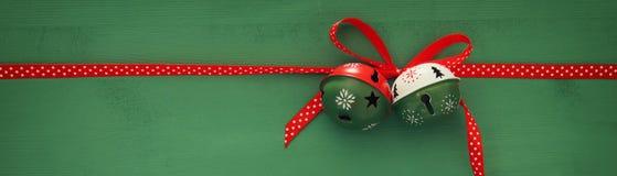 Weihnachtshintergrund mit roten silk traditionellen Band- und Klingelglocken Lizenzfreie Stockfotografie