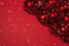 Weihnachtshintergrund mit roten Verzierungen, flaumiger Girlande und fallendem Schnee auf rotem Segeltuchhintergrund Grußkarte de stockfoto