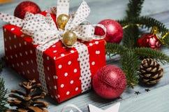 Weihnachtshintergrund mit roter Geschenkbox und Weihnachtsbälle auf Holztisch 2019 Lizenzfreie Stockfotos