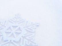 Weihnachtshintergrund mit schöner Schneeflocke auf dem Schnee Stockfotografie
