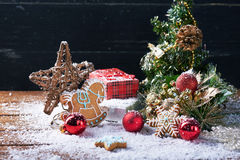 Weihnachtshintergrund mit Schnee, roter Winterdekoration und Schneeflockenplätzchen Lizenzfreies Stockfoto