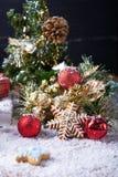 Weihnachtshintergrund mit Schnee, roter Winterdekoration und Schneeflockenplätzchen Stockfoto