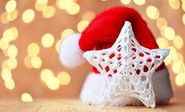 Weihnachtshintergrund mit Stern und Santa Claus-Hut lizenzfreie stockfotos