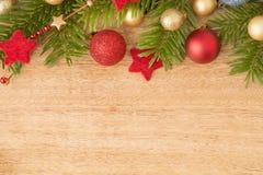 Weihnachtshintergrund mit Tannenbaum, Flitter und Sternen auf Holz Lizenzfreie Stockfotos