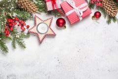 Weihnachtshintergrund mit Tannenbaum, -kerze und -dekorationen auf wh lizenzfreie stockfotografie