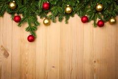 Weihnachtshintergrund mit Tannenbaum und Flitter auf Holz Lizenzfreies Stockfoto