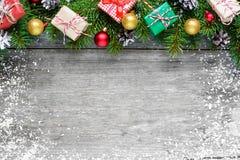 Weihnachtshintergrund mit Tannenzweigen, Dekorationen, Geschenkboxen und Kiefernkegeln Stockfoto