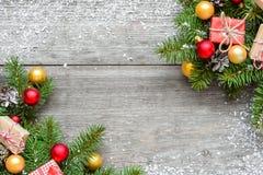 Weihnachtshintergrund mit Tannenzweigen, Dekorationen, Geschenkboxen und Kiefernkegeln Lizenzfreies Stockfoto