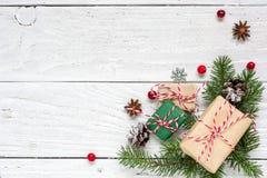 Weihnachtshintergrund mit Tannenzweigen, Dekorationen, Geschenkboxen und Kiefernkegeln Stockbilder