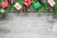 Weihnachtshintergrund mit Tannenzweigen, Dekorationen, Geschenkboxen und Kiefernkegeln auf rustikalem Holztisch Lizenzfreies Stockfoto