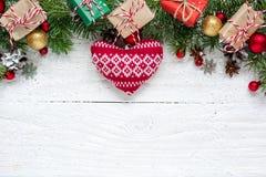 Weihnachtshintergrund mit Tannenzweigen, gestricktem Herzen, Dekorationen, Geschenkboxen und Kiefernkegeln Lizenzfreies Stockbild