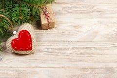 Weihnachtshintergrund mit Tannenzweigen, gestricktem Herzen und Geschenkboxen auf weißem Holztisch Abstraktes Hintergrundmuster d Stockfotografie