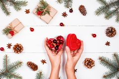 Weihnachtshintergrund mit Tannenzweigen, Kiefernkegel, rote Dekorationen Weibliche Hände, die Weihnachtsgeschenk halten Stockfotos