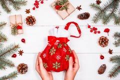 Weihnachtshintergrund mit Tannenzweigen, Kiefernkegel, rote Dekorationen Weibliche Hände, die Weihnachtstasche mit Geschenken hal Stockbilder
