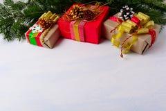 Weihnachtshintergrund mit Tannenzweigen und drei Geschenkboxen Stockfoto