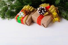 Weihnachtshintergrund mit Tannenzweigen und verzierten Geschenkboxen Stockfotografie