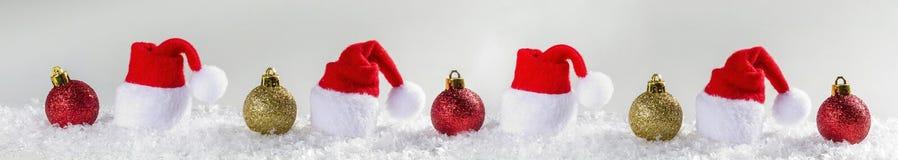 Weihnachtshintergrund mit Weihnachtsbällen und Kappe von Santa Claus Stockbild