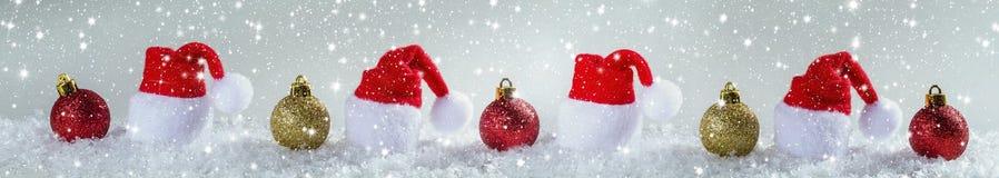 Weihnachtshintergrund mit Weihnachtsbällen und Kappe von Santa Claus Stockfotos
