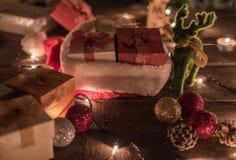 Weihnachtshintergrund mit Weihnachtsball, Geschenkboxen, Sankt-Hut, Ren- und Weihnachtslichtern auf einem hölzernen Hintergrund lizenzfreie stockfotos