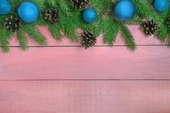 Weihnachtshintergrund mit Weihnachtsbaum, blaue Verzierungen, Kiefernkegel Stockfoto