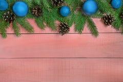 Weihnachtshintergrund mit Weihnachtsbaum, blaue Verzierungen, Kiefernkegel Lizenzfreie Stockfotos
