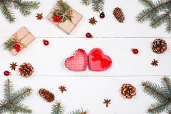 Weihnachtshintergrund mit Weihnachtsgeschenk in der Form des Herzens, Tanne b Stockbilder