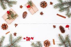 Weihnachtshintergrund mit Weihnachtsgeschenk, Tannenzweige, Kiefernbetrug Lizenzfreie Stockfotos