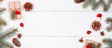 Weihnachtshintergrund mit Weihnachtsgeschenk, Tannenzweige, Kiefernkegel, Schneeflocken, rote Dekorationen Lizenzfreie Stockfotografie