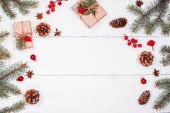 Weihnachtshintergrund mit Weihnachtsgeschenk, Tannenzweige, Kiefernkegel, Schneeflocken, rote Dekorationen Weihnachten und guten  Lizenzfreie Stockfotografie