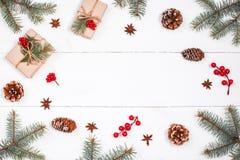 Weihnachtshintergrund mit Weihnachtsgeschenk, Tannenzweige, Kiefernkegel, Schneeflocken, rote Dekorationen Weihnachten und guten  Lizenzfreies Stockfoto