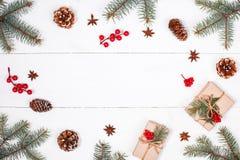 Weihnachtshintergrund mit Weihnachtsgeschenk, Tannenzweige, Kiefernkegel, Schneeflocken, rote Dekorationen Weihnachts- und guten  Stockfoto