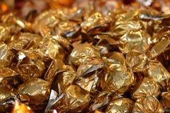 Weihnachtshintergrund, Süßigkeiten eingewickelt in der goldenen Metallfolie Lizenzfreies Stockbild