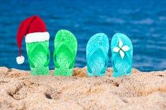 Weihnachtshut auf Flipflops im Sand Stockfoto