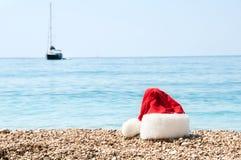 Weihnachtshut liegt auf dem Strand. stockfotografie