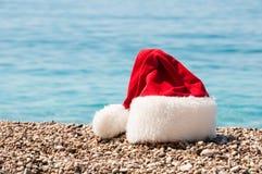 Weihnachtshut liegt auf dem Strand. Stockfoto
